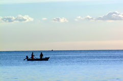 Silhouetted fishermen at sea Royalty Free Stock Images