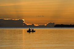 Silhouetted fishermen sitting on a boat Royalty Free Stock Photos