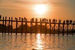 Silhouetted folk på bron för U Bein på solnedgången, Amarapura, Mandalay Myanmar Royaltyfria Bilder