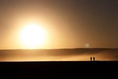 Silhouetted folk på solnedgången Royaltyfria Bilder