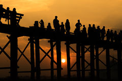 Silhouetted folk som korsar U-beinbron med solnedgången, longesna royaltyfri fotografi