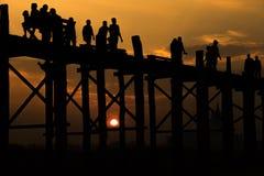 Silhouetted folk som korsar U-beinbron med solnedgången, longesna arkivbilder