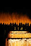 Silhouetted fountain with dancing water. Silhouetted spectators watching the light and fountain show at Montjuic in Barcelona, Spain Stock Image