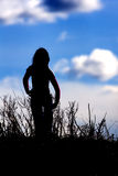 Silhouetted girl against blue sky. Stock Image