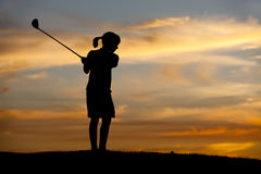Silhouetted girl swings club. A young girl in silhouette at sunset swings the golf club at the ball Stock Images