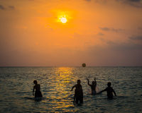 Silhouetted group of boy are playing a ball in the sea Stock Photography