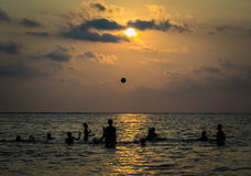 Silhouetted group of boy are playing a ball in the sea Stock Image