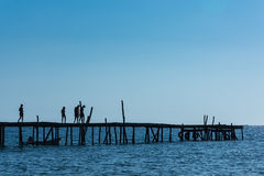 A silhouetted group of friends walk along an old wooden pier Royalty Free Stock Photography