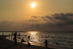 Silhouetted group of people on the beach and in the sea Royalty Free Stock Images