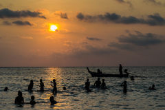 Silhouetted group of people are playing in the sea Royalty Free Stock Photos
