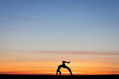 Silhouetted gymnast doing bow in sunset Stock Images