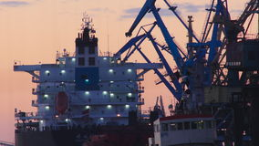 Silhouetted harbor cranes loading freight into a ship. During golden hour stock footage