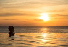 Silhouetted head against infinity edge pool Stock Photos