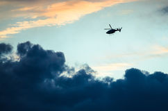 Silhouetted Helicopter Flying Across a Sunset Sky. Silhouetted Helicopter Flying Across a Dark Sunset Sky Stock Photos