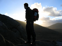 Silhouetted hiker. Hiker silhouetted against the morning sky in the hills of Ireland Stock Photos
