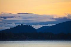 Silhouetted hills around Shuswap Lake and colorful orange sky, British Columbia. Canada stock image