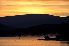 Silhouetted hills around Shuswap Lake and colorful orange sky, British Columbia. Canada royalty free stock photo