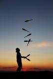 Silhouetted jonglör i solnedgång Royaltyfri Bild