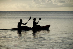 Silhouetted kayakers on the ocean Stock Images