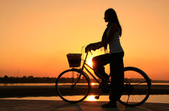 Silhouetted kvinna med cykeln på Mekong River Royaltyfri Foto