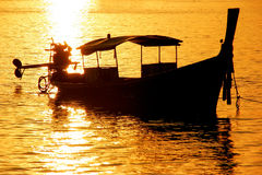 Silhouetted longtail boat at sunrise on Ao Ton Sai, Phi Phi Don. Island, Krabi Province, Thailand. Koh Phi Phi Don is part of a marine national park Royalty Free Stock Image