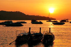 Silhouetted longtail boats at sunrise on Ao Ton Sai, Phi Phi Don. Island, Krabi Province, Thailand. Koh Phi Phi Don is part of a marine national park Royalty Free Stock Photography