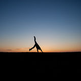 Silhouetted man doing a cartwheel at sunset Royalty Free Stock Photos