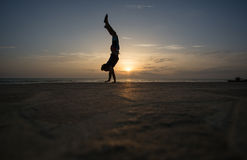 Silhouetted man doing handstand in sunset Royalty Free Stock Photos