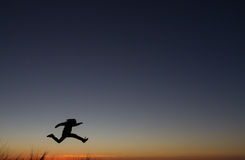 Silhouetted of man jumping in sunset Stock Photos
