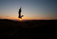 Silhouetted man jumping in sunset Royalty Free Stock Photo