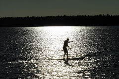 A silhouetted man paddle boarding on a Saskatchewan lake.  Royalty Free Stock Images