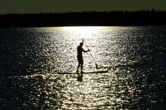 A silhouetted man paddle boarding on a Saskatchewan lake.  stock photos