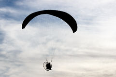 Silhouetted man with paraglider Stock Images