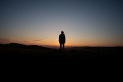 Silhouetted man standing in sunset Royalty Free Stock Photo
