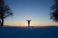 Silhouetted man standing in winter landscape Stock Photo