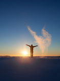 Silhouetted man standing in winter landscape and throwing snow Stock Image