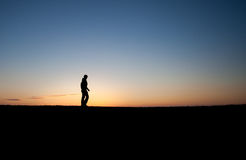 Silhouetted man in sunset Stock Image