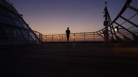 Silhouetted Man Walks on Deck of Cruise Ship at Sunset. 8774 A silhouetted man walks on the deck of a large cruise ship at sunset stock footage