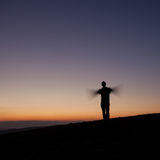 Silhouetted man waving with arms in sunset royalty free stock photos