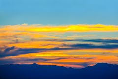 Silhouetted of mountain with colorful sky. Silhouetted of mountain with dramatic colorful sky in sunset Stock Photo