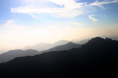 Silhouetted mountains and sky. Scenic view of silhouetted mountain range with blue sky and cloudscape background Royalty Free Stock Photos