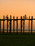 Silhouetted people with bikes on U Bein Bridge at sunset, Amarap Royalty Free Stock Photos