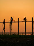 Silhouetted people with bikes on U Bein Bridge at sunset, Amarap Stock Images