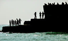 Silhouetted People On Brighton Coast. Silhouetted people on a sea defence on the Brighton coast Stock Images