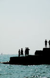 Silhouetted People On Brighton Coast. Silhouetted people on a sea defence on the Brighton coast Stock Photo