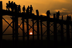 Silhouetted people crossing U bein bridge with sunset,The longes Stock Images