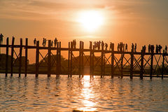 Silhouetted people on U Bein Bridge at sunset, Amarapura, Mandalay Myanmar. Silhouetted people on U Bein Bridge at sunset, Amarapura, Mandalay region, Myanmar Royalty Free Stock Images