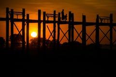 Silhouetted people on U Bein Bridge at sunset, Amarapura. Stock Image
