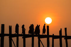 Silhouetted people on U Bein Bridge at sunset. Stock Image