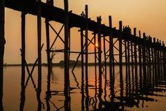 Silhouetted people on U Bein Bridge at sunset, Amarapura, Mandalay region, Myanmar Stock Image